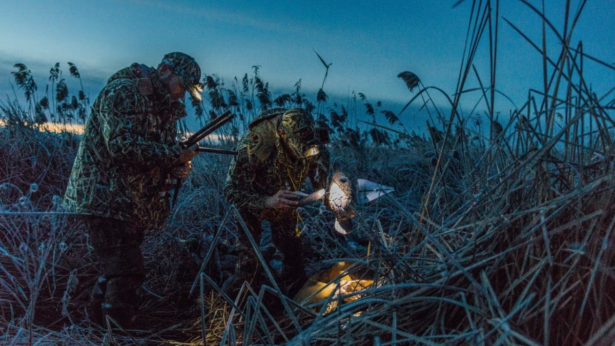 Duck hunters setting up a decoy